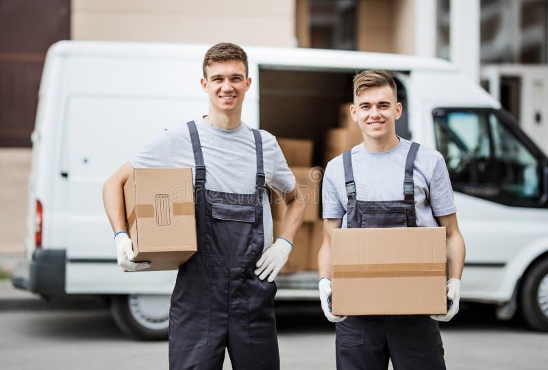穿制服的两名年轻英俊的微笑的工作者在搬运车拿着箱子的箱子前面充分站立  免版税库存照片