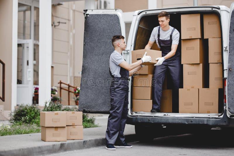 穿制服的两名幼小英俊的搬家工人充分卸载搬运车箱子 议院移动,搬家工人服务 图库摄影