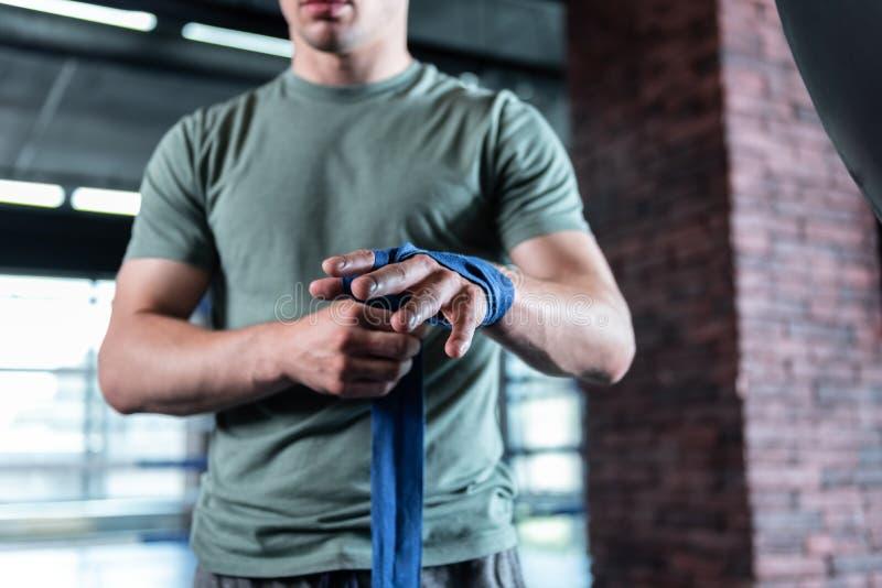 穿卡其色的衬衣的坚强的运动员拿着蓝色腕子套 免版税库存照片