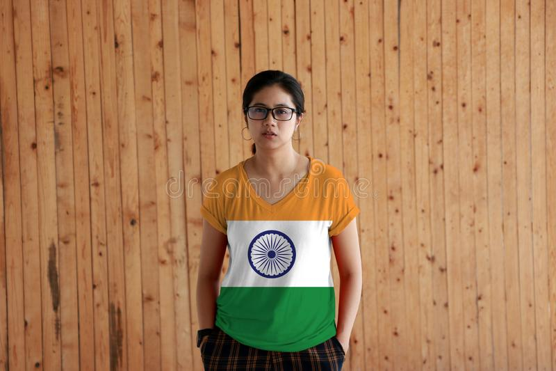 穿印度旗子颜色衬衣和站立用在裤兜的两只手的妇女在木墙壁背景 免版税库存图片