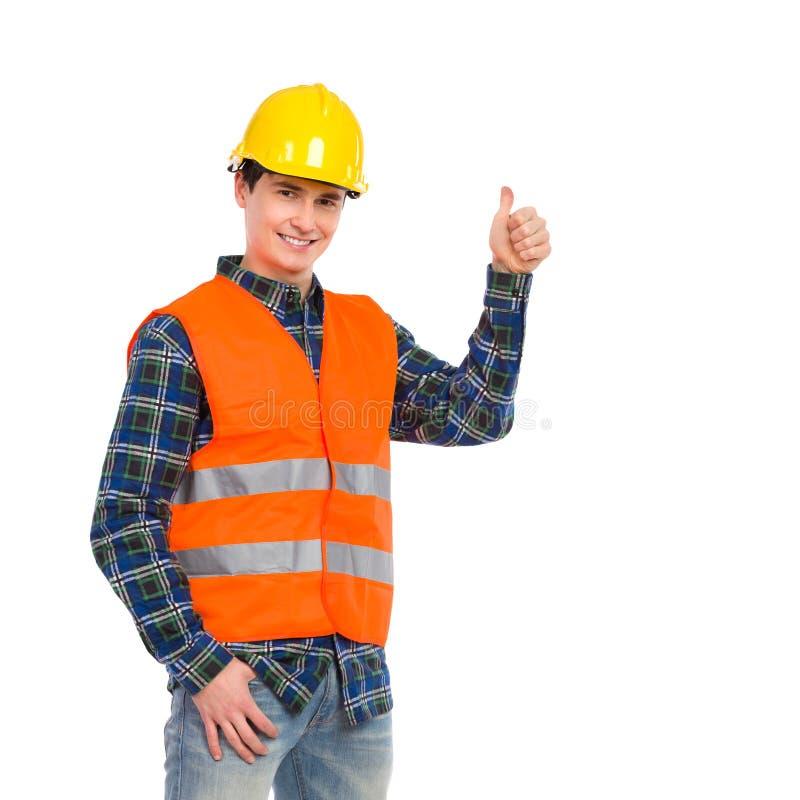 穿反射性衣物和显示赞许的建筑工人。 图库摄影