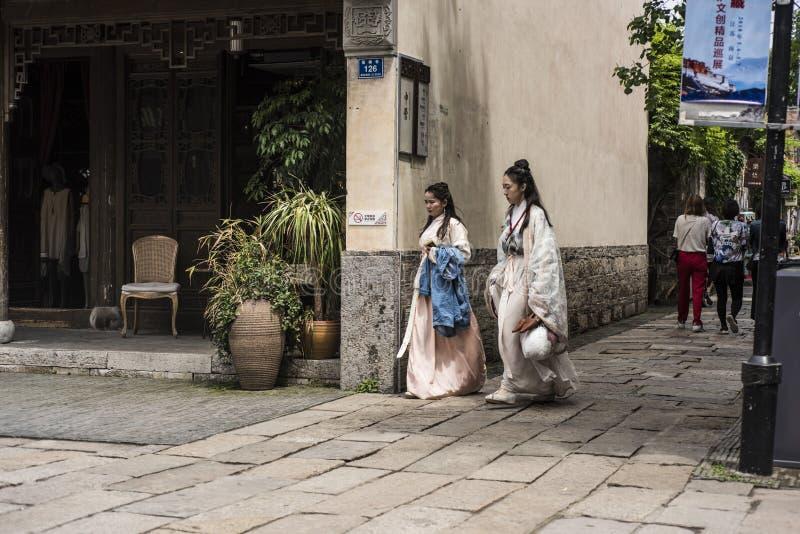 穿古老服装的两个女孩走在风景区 图库摄影