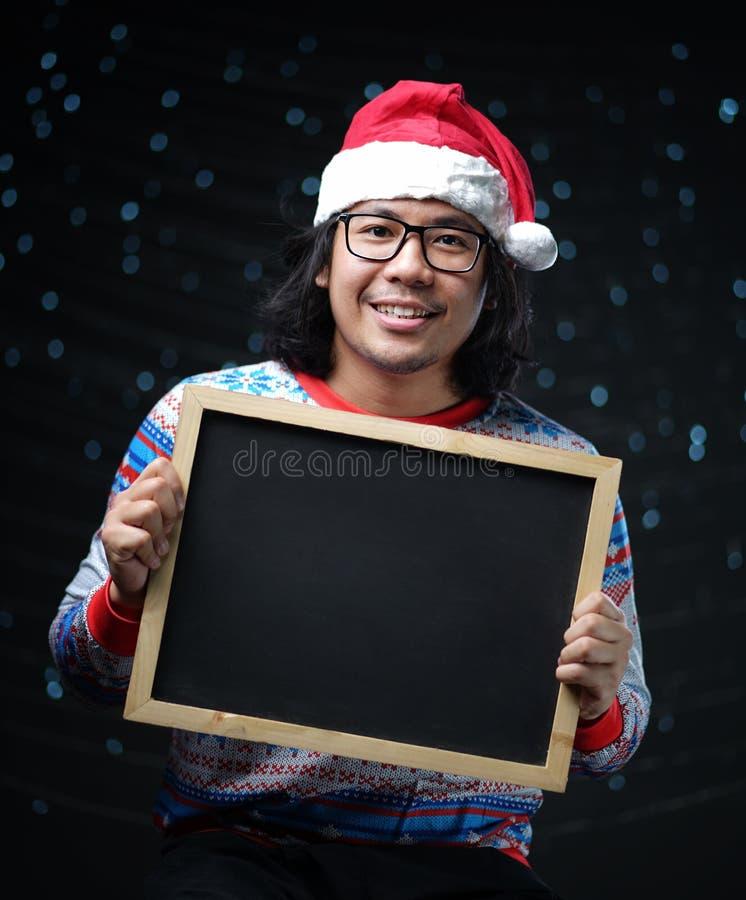 穿圣诞老人帽子和圣诞节毛线衣的亚裔人举行Blackb 库存照片
