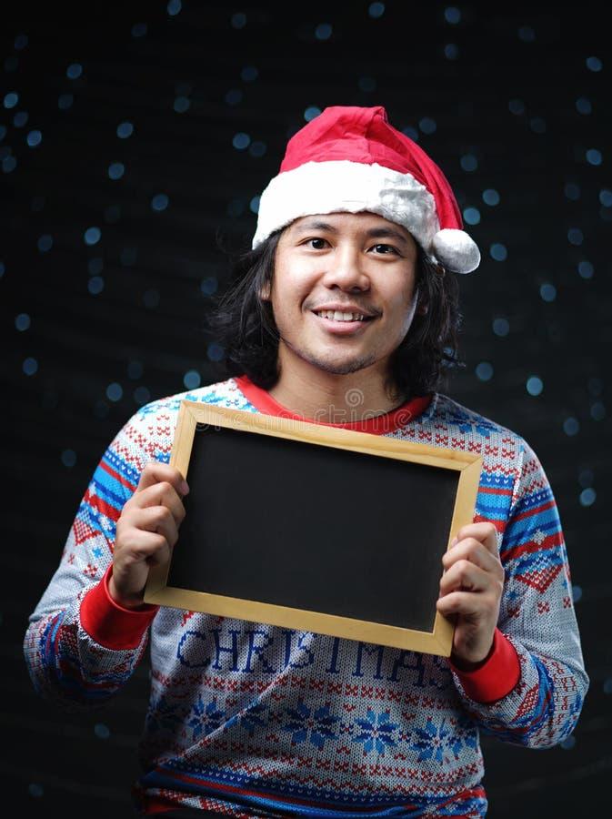 穿圣诞老人帽子和圣诞节毛线衣的亚裔人举行Blackb 免版税库存照片