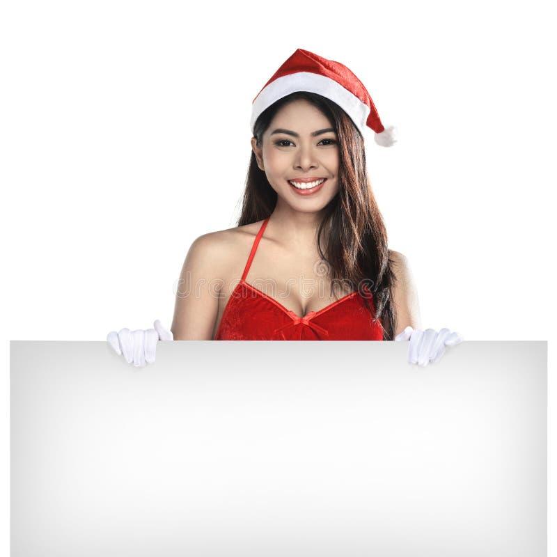 穿圣诞老人服装的年轻可爱的亚裔妇女拿着空白的广告牌 免版税图库摄影