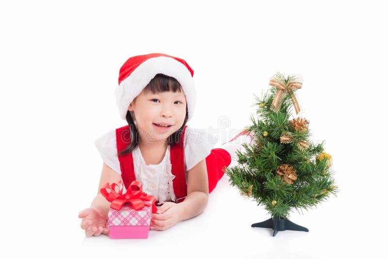 穿圣诞老人礼服的小女孩说谎在地板上 库存照片
