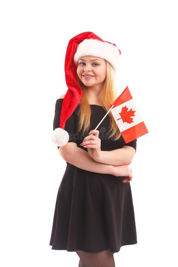穿在一个圣诞老人帽子的一个美丽的少妇的画象一件黑礼服有一面旗子的在白色隔绝的手上 免版税库存照片