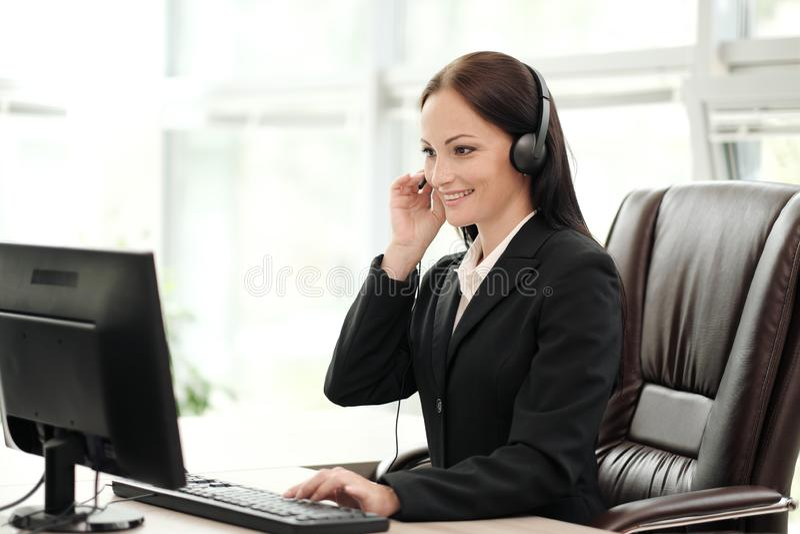穿在一件黑夹克的一名年轻可爱的妇女一件黑夹克坐在她的在一把行政椅子的书桌 ??a 免版税库存图片
