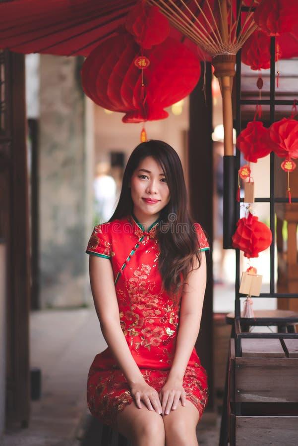 穿在农历新年的逗人喜爱的微笑的亚裔中国妇女Cheongsam传统红色礼服 免版税库存照片