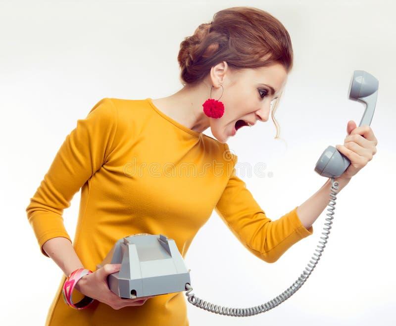 穿在减速火箭的样式的少妇黄色礼服与老电话 库存图片