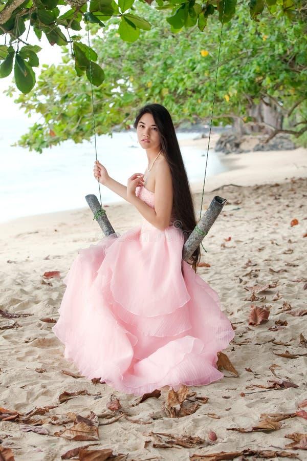 穿在夏威夷海滩的少妇长的桃红色礼服 库存图片