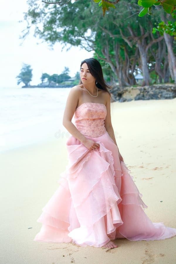 穿在夏威夷海滩的少妇长的桃红色礼服 免版税图库摄影
