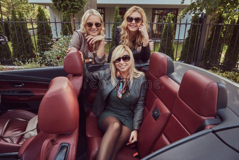 穿在太阳镜的三个白肤金发的女性朋友流行的服装在夏天旅行的敞蓬车汽车 假期和 免版税库存图片