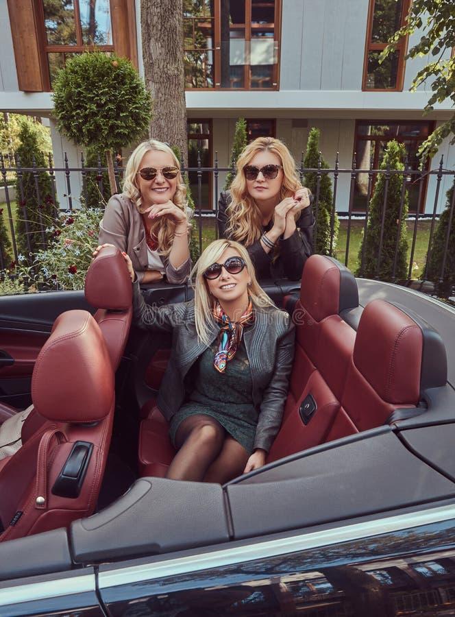 穿在太阳镜的三个白肤金发的女性朋友流行的服装在夏天旅行的敞蓬车汽车 假期和 库存照片