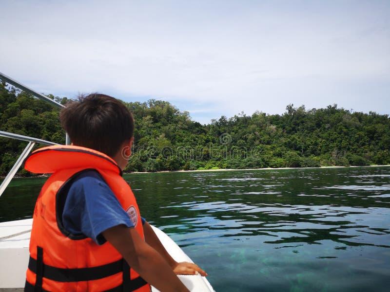 穿在小船的一个小男孩一个救生背心安全预防措施的在室外游览期间 免版税库存照片