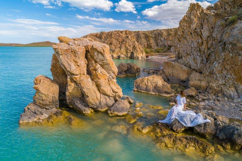 穿在岩石的年轻女人的鸟瞰图一件白色礼服 与女孩的夏天海景,海滩,美丽的波浪,岩石,蓝色 免版税库存图片