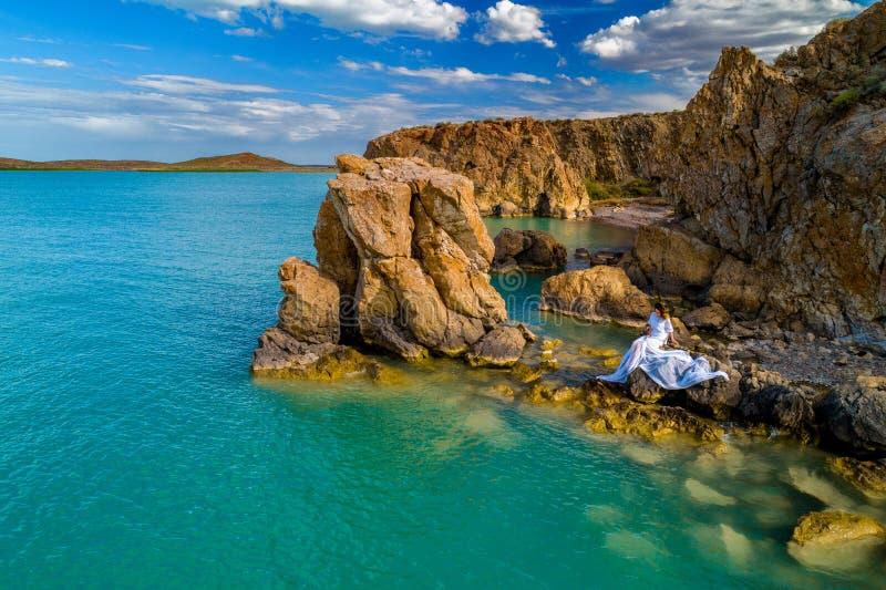 穿在岩石的年轻女人的鸟瞰图一件白色礼服 与女孩的夏天海景,海滩,美丽的波浪,岩石,蓝色 免版税图库摄影