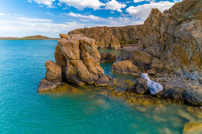 穿在岩石的年轻女人的鸟瞰图一件白色礼服 与女孩的夏天海景,海滩,美丽的波浪,岩石,蓝色 库存图片