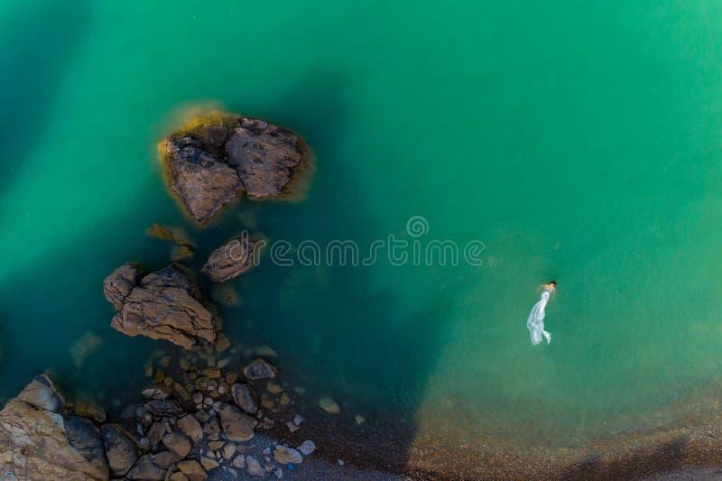穿在岩石的年轻女人的鸟瞰图一件白色礼服 与女孩的夏天海景,海滩,美丽的波浪,岩石,蓝色 库存照片