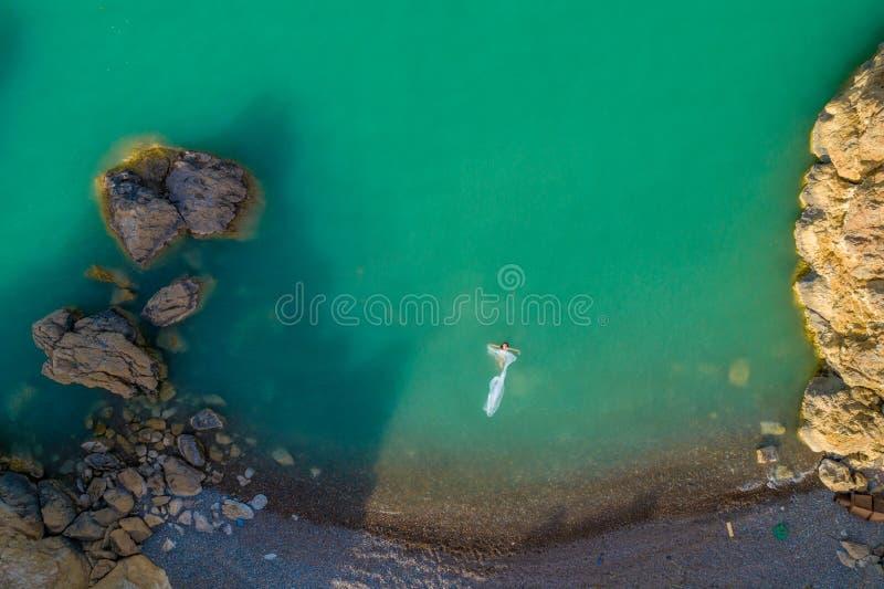 穿在岩石的年轻女人的鸟瞰图一件白色礼服 与女孩的夏天海景,海滩,美丽的波浪,岩石,蓝色 免版税库存照片