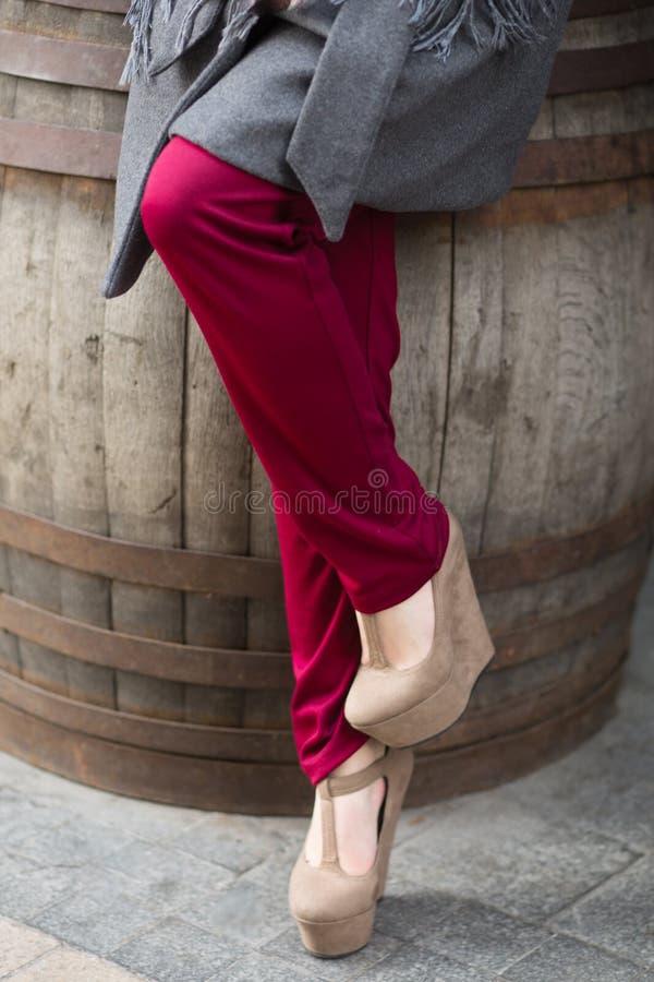 穿在平台和marsala裤子的女性腿米黄鞋子 免版税库存图片
