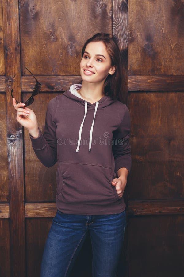 穿在木墙壁前面的妇女洋红色运动衫 免版税库存图片