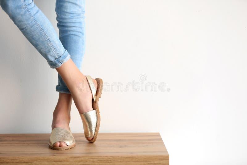 穿在桌上的少妇典雅的鞋子 免版税库存照片
