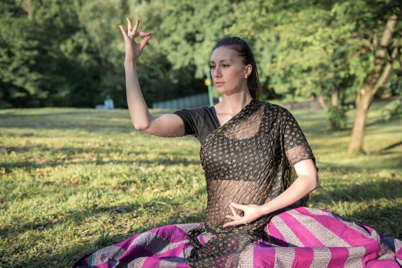穿在莲花姿势的俏丽的深色的妇女印地安礼服 免版税库存照片