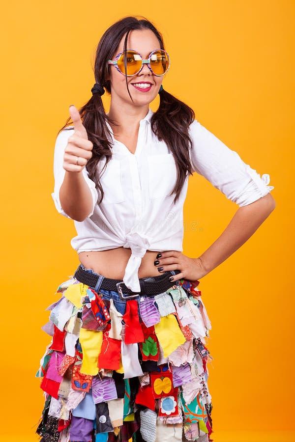 穿在黄色背景的美丽的年轻女人质朴的服装 图库摄影