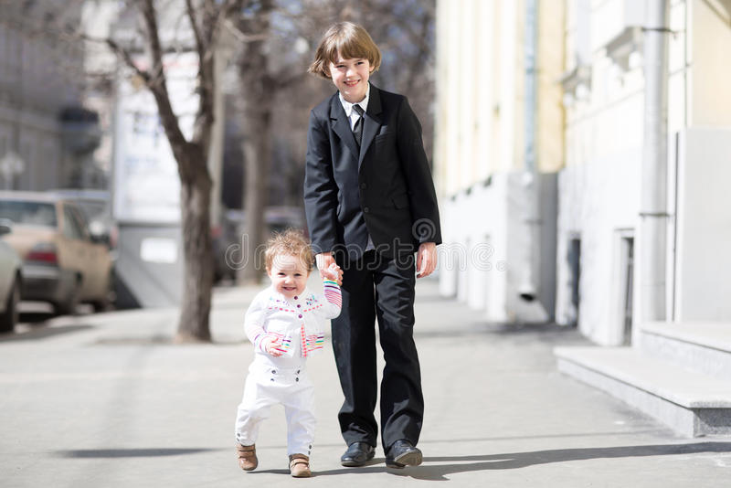 穿在晴朗的街道上的孩子正式衣裳 免版税库存照片