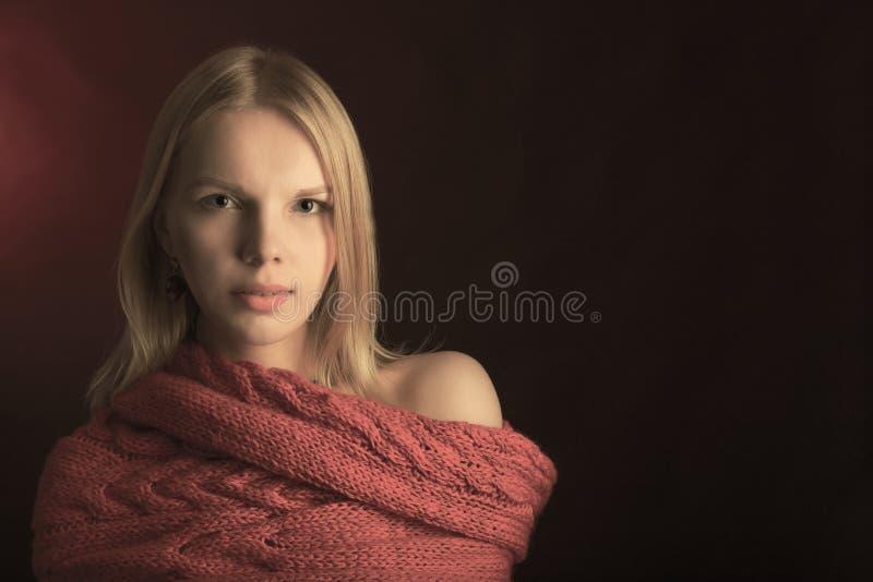 穿在黑背景的女孩画象红色围巾 库存图片
