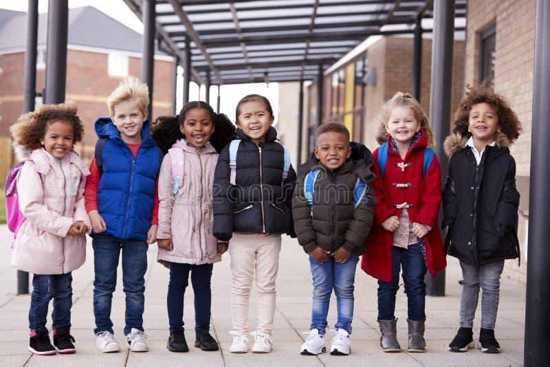穿外套和运载书包的一个小组微笑的年轻不同种族的学校孩子连续站立在他们之外的走道 免版税库存图片
