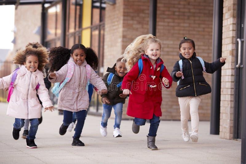 穿外套和运载书包的愉快的年轻学校女孩运行在有他们的同学的一个走道在他们的婴儿sch之外 库存图片