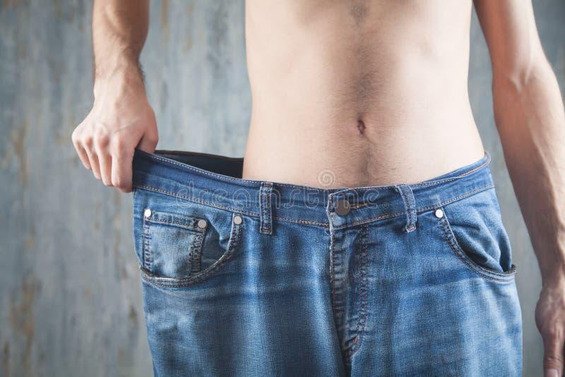 穿大号牛仔裤的男子 减重 库存照片