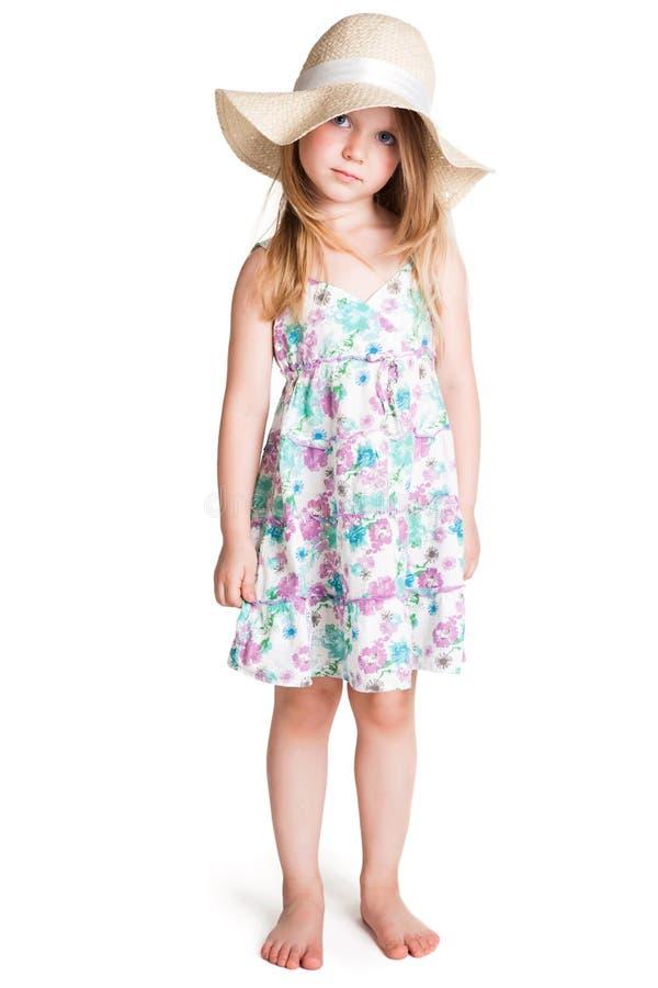 穿大白色帽子和礼服的小白肤金发的女孩 图库摄影