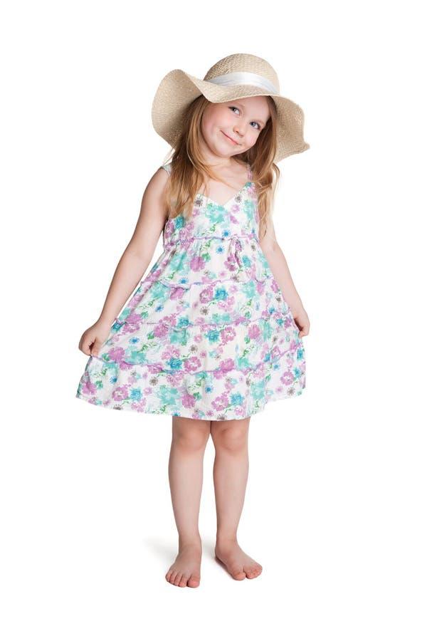 穿大白色帽子和礼服的微笑的小白肤金发的女孩 免版税图库摄影