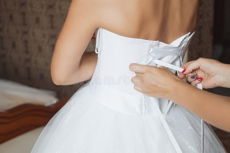 穿婚礼礼服的母亲帮助 库存图片