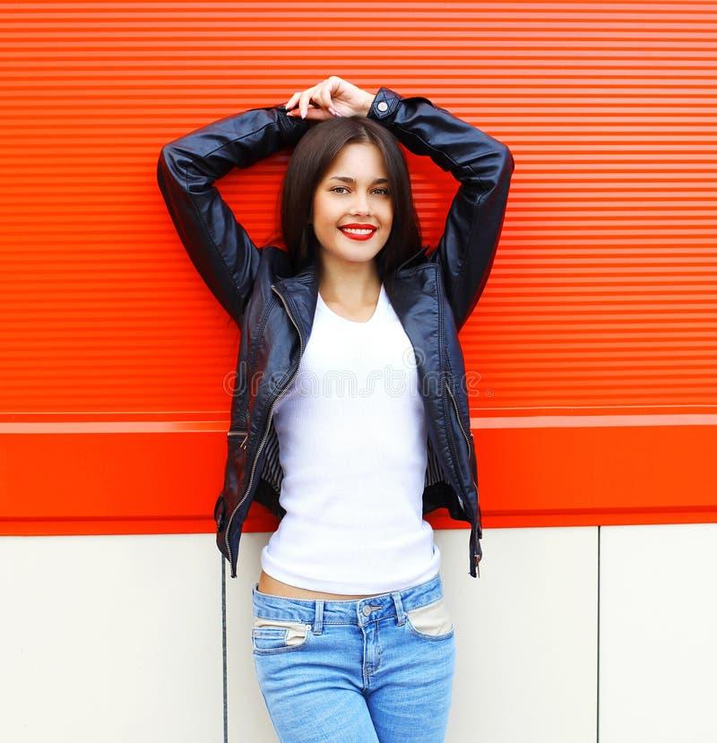 穿岩石黑色皮夹克和牛仔裤的画象美丽的微笑的年轻深色的妇女摆在城市 免版税库存照片