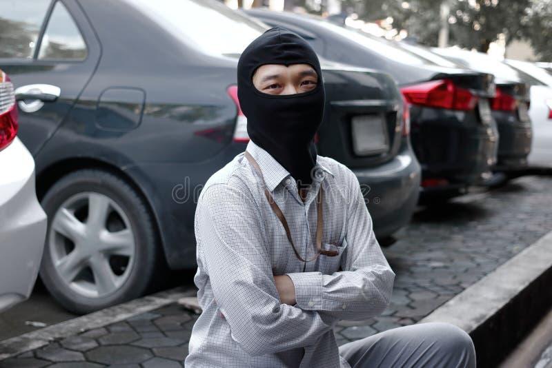 穿巴拉克拉法帽的被掩没的夜贼准备好对抢劫反对汽车背景 保险罪行概念 免版税图库摄影