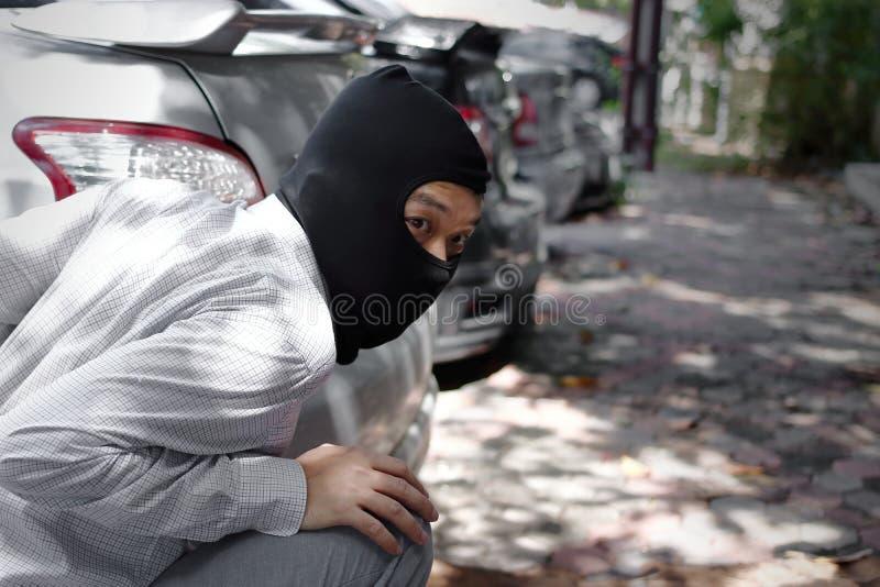 穿巴拉克拉法帽的被掩没的夜贼准备好对抢劫反对汽车背景 保险罪行概念 库存照片