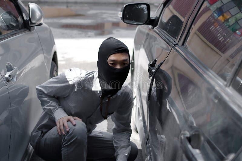 穿巴拉克拉法帽的被掩没的夜贼准备好对抢劫反对汽车背景 保险罪行概念 库存图片