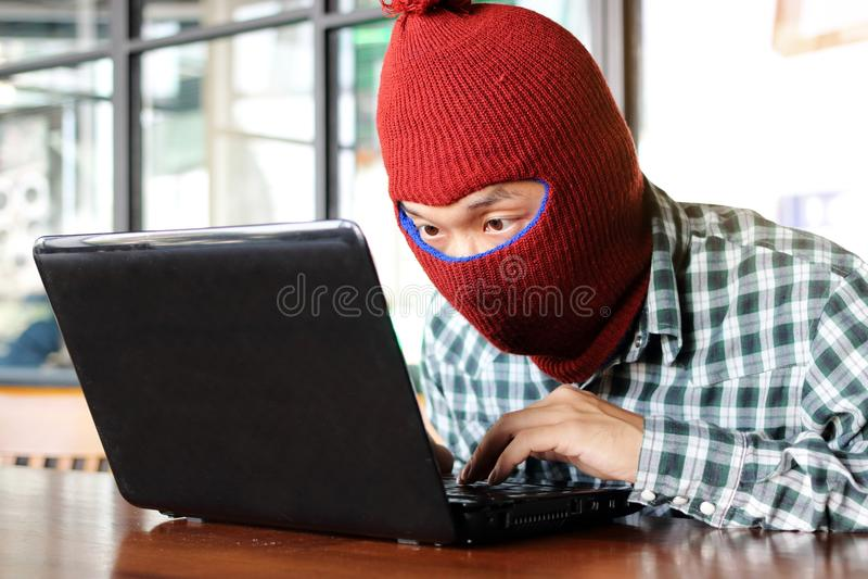 穿巴拉克拉法帽的被掩没的黑客窃取从膝上型计算机的重要性数据 互联网罪行概念 库存图片