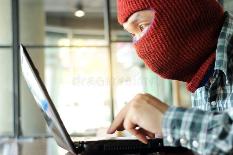 穿巴拉克拉法帽的被掩没的黑客窃取从膝上型计算机的重要性数据 互联网罪行概念 免版税库存图片