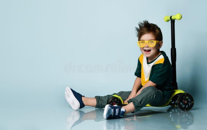 穿彩色T恤、黄色太阳镜、灰色牛仔裤、运动鞋的小男人 微笑,坐在滑板车上 蓝色背景 库存图片