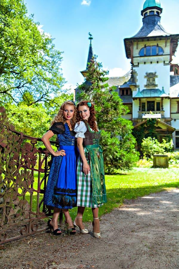 穿慕尼黑啤酒节少女装的两个美丽的女孩 库存照片