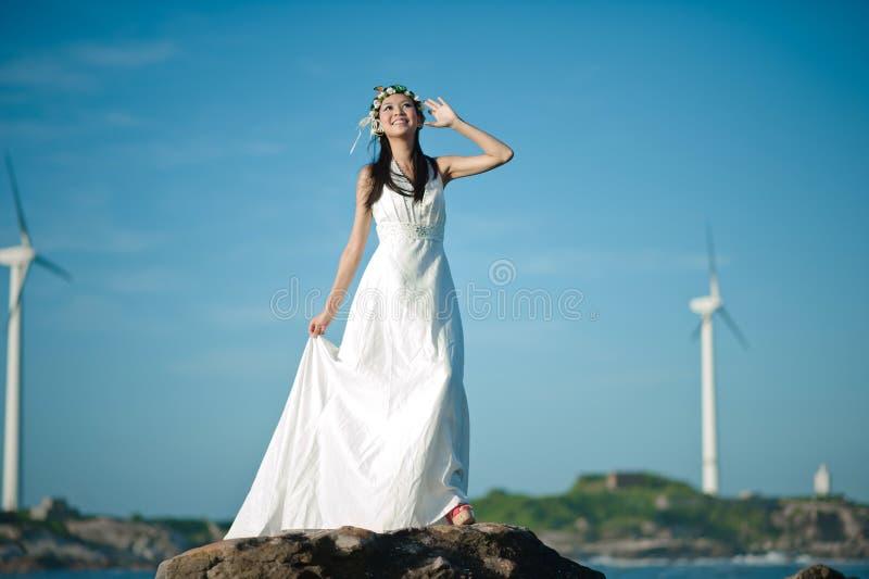 穿戴了享用海风的美丽的亚裔女孩在白色礼服由海 免版税库存图片