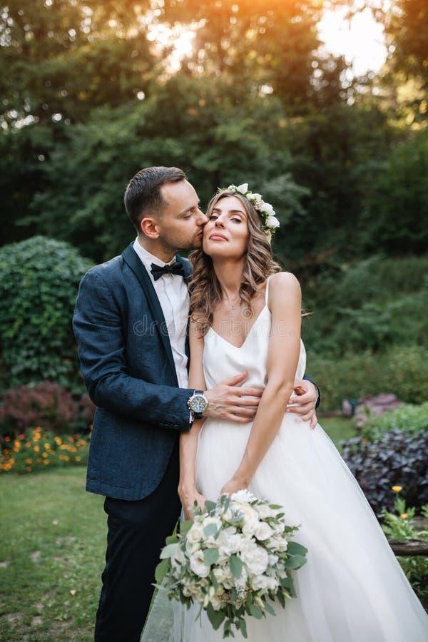穿戴了亲吻与她一套白色婚礼礼服的美丽的新娘的新郎在一套时髦的衣服本质上婚姻室外仪式 库存图片