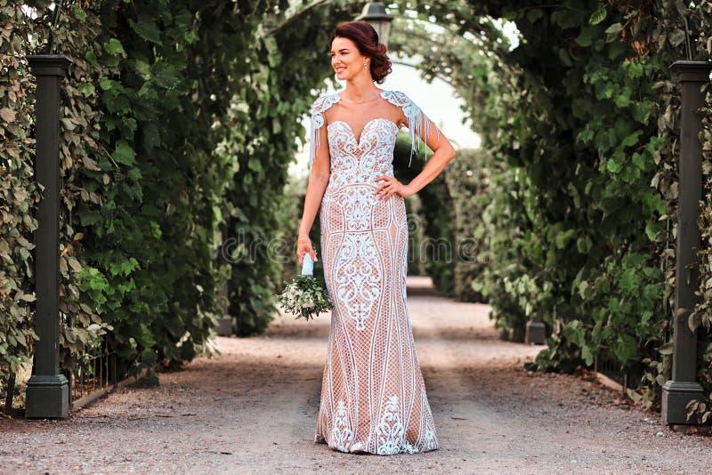 穿戴了婚姻花束的愉快的新娘在一件惊人的礼服举行,当站立在美丽的庭院里时 免版税库存照片