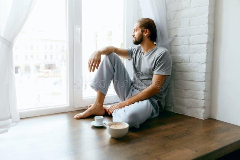 穿戴女孩褂子早晨白色的咖啡杯 享受热的饮料的人在窗口附近 免版税库存图片