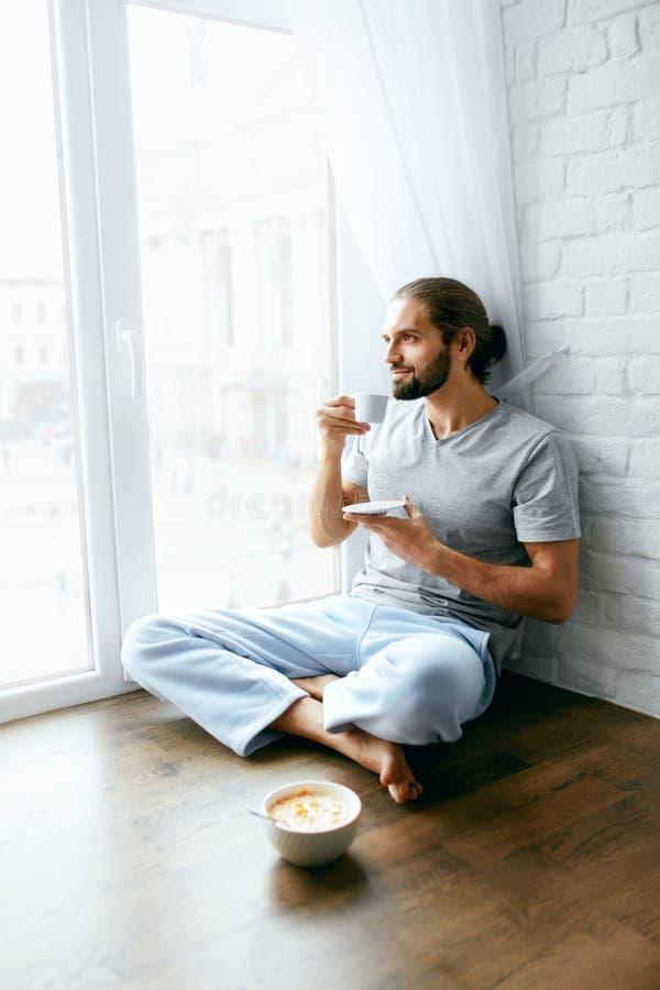 穿戴女孩褂子早晨白色的咖啡杯 享受热的饮料的人在窗口附近 免版税库存照片